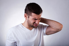 Man with neck pain. Young man with strong neck pain, horizontal Stock Photo