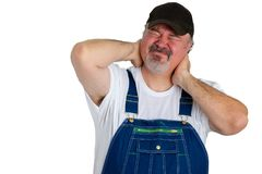 Man with neck pains or a work related injury. Workman in bib overalls with neck pains or a work related injury gripping the back of his head grimacing in pain stock image