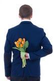 Man nederlagbuketten av blommor bak hans baksida som isoleras på vit Royaltyfria Foton