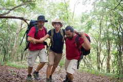 Man need help to get up while hiking. Asian man need help to get up while hiking in the forest. tired man supported by friends Stock Photos