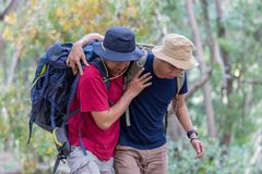 Man need help to get up while hiking. Asian men need help to get up while hiking in the forest. tired men supported by friends Royalty Free Stock Photos