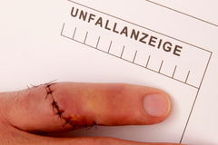 Man with needled finger fills out a accident report Stock Photography