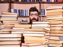 Man nerd på förvånad framsida mellan högar av böcker i arkiv, bokhyllor på bakgrund Lärare eller student med skägget arkivfoton