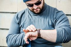 Man nervously looking at his watch. Man dressed with grey top and a hat, with glasses looking nervously at his watch - brick background Stock Image