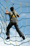 Man in net. Man climbing in rope net stock photography