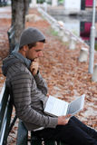 Man with netbook deep in thoughts. Man sitting on a Bench with netbook smiling Royalty Free Stock Photography
