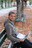 Man with netbook smiling. Man sitting on a Bench with netbook smiling Royalty Free Stock Photo