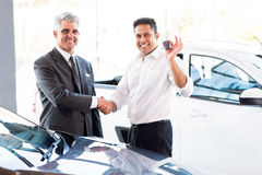 Man new car key. Happy indian men showing new car key while handshaking with salesman Stock Photos