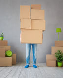 Man New Home Moving Day House Concept. Man carrying boxes into new home. Moving house day and express delivery concept Royalty Free Stock Images