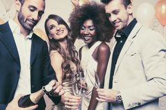 Man, on new year or birthday party opening bottle of champagne. Together with his friends stock images