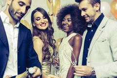 Man, on new year or birthday party opening bottle of champagne. Together with his friends stock image