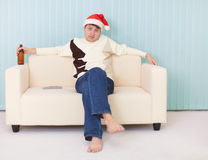 Man in a New Year's cap sits on sofa with bottle Royalty Free Stock Photo