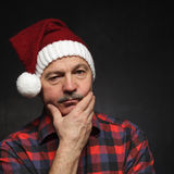 Man in New Year's cap looks sad. Bad mood before Christmas Stock Photos