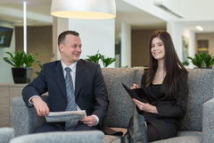 A man with newspaper and girl with notepad talking Stock Photography