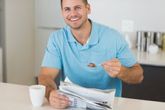 Man with newspaper having cereals at table Royalty Free Stock Photos