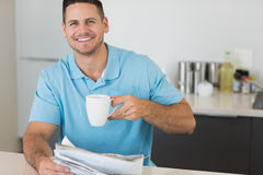 Man with newspaper holding coffee cup at table Stock Photo