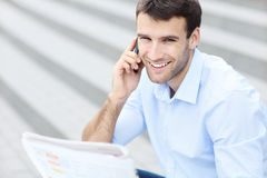 Man with newspaper and mobile phone Stock Images