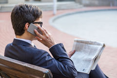 Man with newspaper on phone Stock Photos