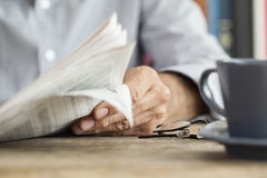 Man newspaper reading on table Stock Photos