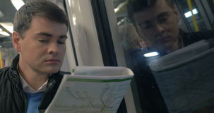 Man with newspaper traveling in metro train. Young man having ride in subway train. He sitting by the window and reading newspaper or city guide stock video footage