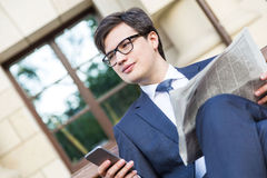 Man with newspaper using phone Royalty Free Stock Image