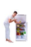 The man next to fridge full of food Royalty Free Stock Photos