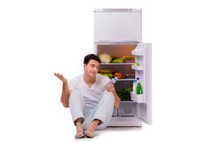 The man next to fridge full of food. Man next to fridge full of food Royalty Free Stock Images