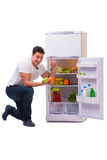 The man next to fridge full of food. Man next to fridge full of food Royalty Free Stock Image