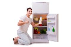 The man next to fridge full of food Stock Photo
