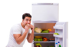The man next to fridge full of food. Man next to fridge full of food Stock Photography