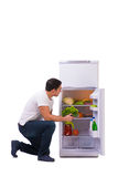 The man next to fridge full of food. Man next to fridge full of food Royalty Free Stock Photo