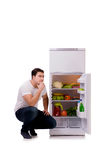The man next to fridge full of food. Man next to fridge full of food Stock Photos