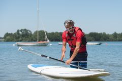 Man next to stand-up paddle board on lake stock image