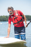 Man next to stand-up paddle board on lake Stock Photos