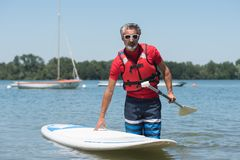 Man next to stand-up paddle board on lake Royalty Free Stock Photography