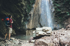 Man next to a waterfall after mountain trekking Royalty Free Stock Photos
