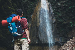 Man next to a waterfall after mountain trekking Royalty Free Stock Image