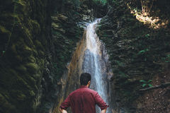 Man next to a waterfall after mountain trekking Royalty Free Stock Photo