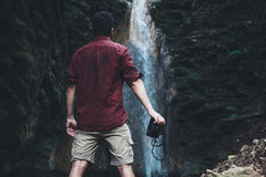 Man next to a waterfall after mountain trekking Stock Photography
