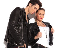 Man next to woman pulling her jacket's collar. Side view of a fashion couple in leather jackets standing in studio and look away from the camera, men is looking Royalty Free Stock Photo