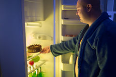 Man at night overstep and take whole chocolate cake from refrige Royalty Free Stock Photo