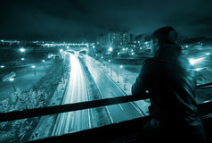 Man in night urban scene. Nigth urban scene with young man,road and tunnel royalty free stock images