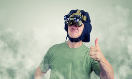 Man in a night-vision device shows thumb. All cool! Royalty Free Stock Image