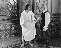 Man in a nightgown arguing with a man  in the hallway. (All persons depicted are no longer living and no estate exists. Supplier grants that there will be no Stock Photo