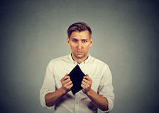 Man with no money holding empty wallet Royalty Free Stock Image