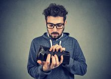 Man with no money holding an empty wallet. Sad hipster man with no money holding an empty wallet royalty free stock photography