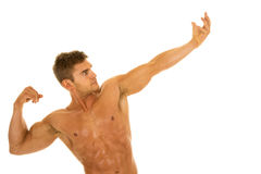 Man no shirt flex arm out look up. A man flexing his arms and body without a shirt on Royalty Free Stock Photo