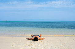 Man with no shirt lay down on the beach Stock Images