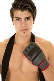 Man no shirt red shorts one glove up. A man without a shirt on wearing gloves ready to box Royalty Free Stock Photos