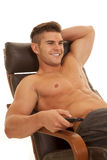 Man no shirt remote control sit point lean back smile Royalty Free Stock Image